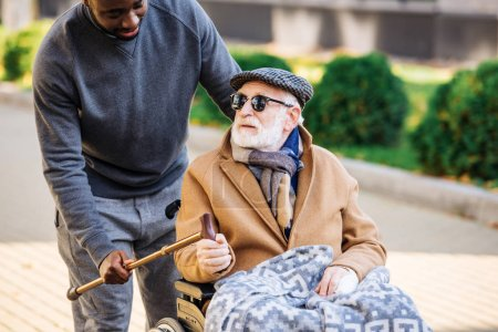 Photo for Young african american man giving walking stick to senior disabled man in wheelchair on street - Royalty Free Image