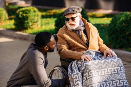 senior disabled man in wheelchair and african american nurse chatting on street