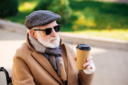 close-up portrait of senior disabled man in wheelchair holding paper cup of coffee on street