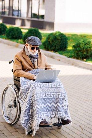 Photo pour Homme handicapé âgé concentré en fauteuil roulant en utilisant un ordinateur portable dans la rue - image libre de droit