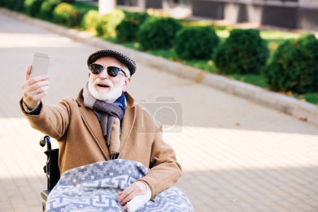 happy senior disabled man in wheelchair taking selfie on street