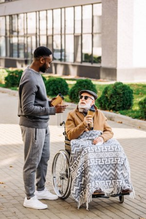 senior disabled man in wheelchair with plaid and african american man spending tome together on street with paper cups of coffee