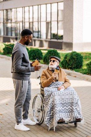 Photo pour Principal désactivé homme en fauteuil roulant avec plaid et afro-américain de passer ensemble des tome sur rue avec des gobelets en papier de café - image libre de droit