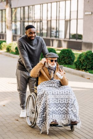 principal désactivé homme en fauteuil roulant écoute rêvant avec smartphone et écouteurs avec cuidador african american sur la rue