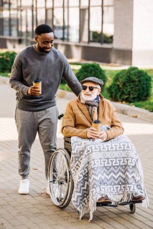 Photo for Smiling senior disabled man in wheelchair with plaid and african american man riding by street with paper cups of coffee - Royalty Free Image