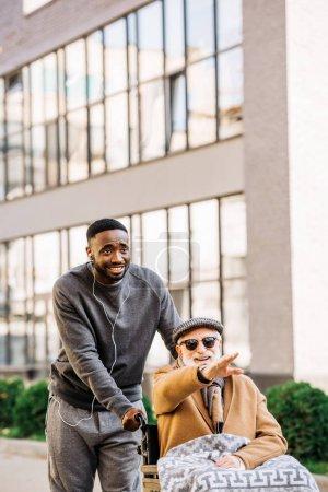 happy senior disabled man in wheelchair with plaid and african american man riding by street and looking somewhere