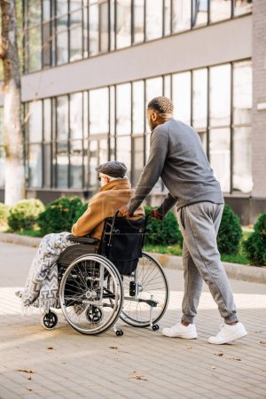 senior disabled man in wheelchair with plaid and cuidador riding by street