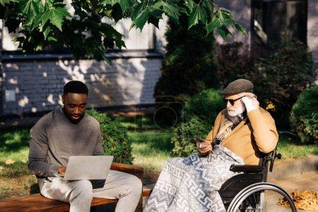 Photo pour Principal désactivé homme en fauteuil roulant et les jeunes Afro-américain à l'aide de gadgets ensemble sur la rue - image libre de droit