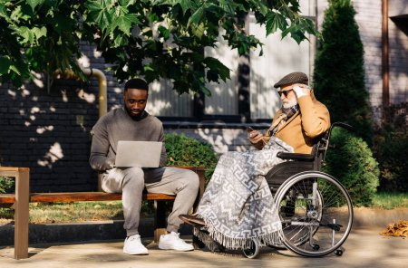 senior disabled man in wheelchair and african american man using gadgets together on street