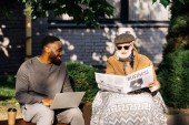 happy senior disabled man reading business newspaper in wheelchair while african american man using laptop on street