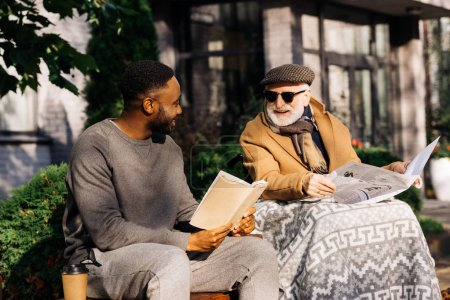 senior disabled man in wheelchair and african american man reading book and newspaper together on street