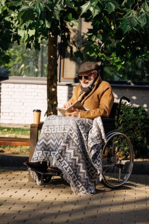 Photo for Senior disabled man in wheelchair with paper cup of coffee reading book on street - Royalty Free Image