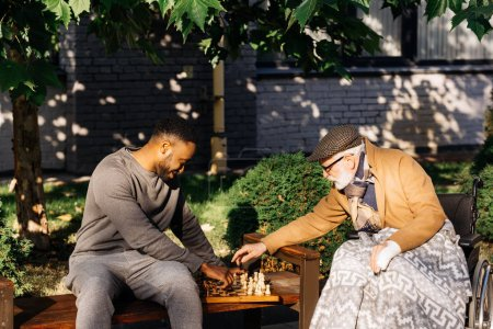 senior disabled man in wheelchair and african american nurse playing chess together on street