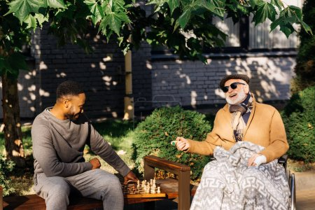 senior disabled man in wheelchair and african american cuidador playing chess together on street