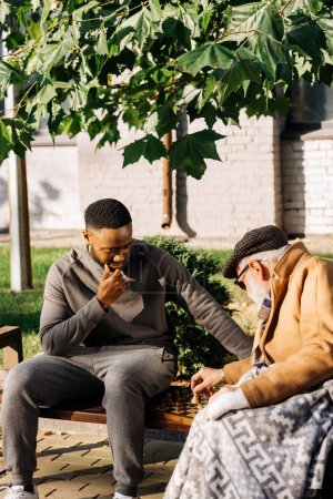 Photo for Senior man and young african american cuidador playing chess together on street - Royalty Free Image