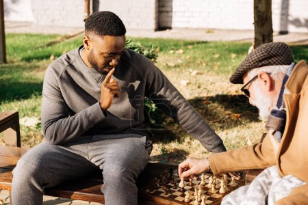 senior homme et réfléchie afro-américain homme jouant aux échecs ensemble dans la rue