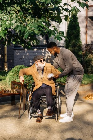 african american man helping senior disabled man to get up from wheelchair on street