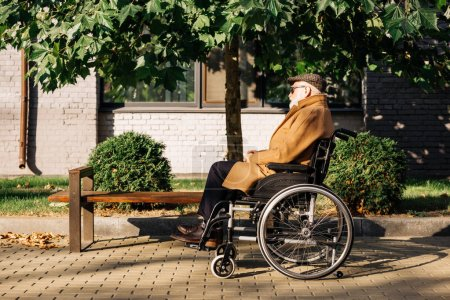 side view of senior disabled man sitting in wheelchair on street