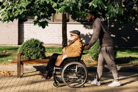 side view of senior disabled man in wheelchair and nurse riding on street