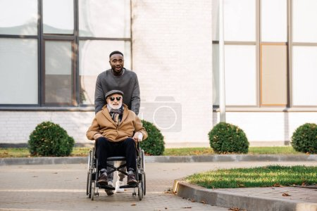 happy senior disabled man in wheelchair and african american man riding by street together