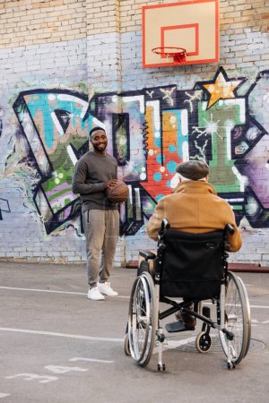 back view of senior disabled man in wheelchair looking at african american man playing basketball on street
