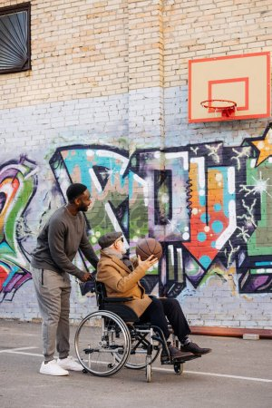 senior disabled man in wheelchair and happy african american man playing basketball together on street