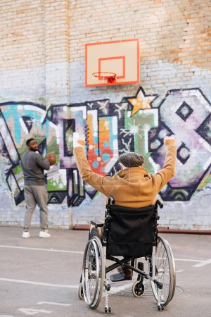 Photo for Back view of celebrating senior disabled man in wheelchair looking at african american man playing basketball on street - Royalty Free Image