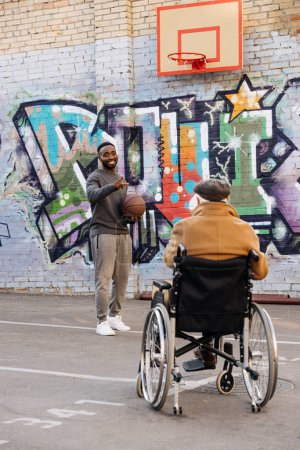 rear view of senior disabled man in wheelchair looking at happy african american man playing basketball on street