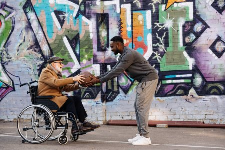side view of senior disabled man in wheelchair and african american man playing basketball together on street