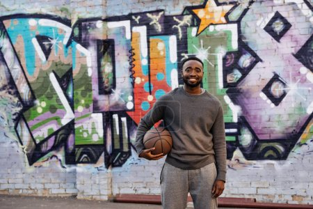 Photo for Handsome african american man with basketball ball looking at camera on street in front of colorful graffiti - Royalty Free Image