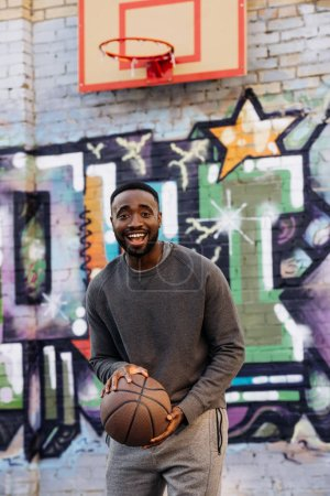 happy african american man with basketball ball looking at camera on street in front of colorful graffiti