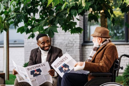 happy senior disabled man in wheelchair and african american man reading newspapers together on street