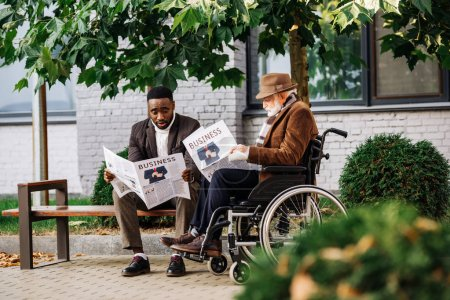 senior disabled man in wheelchair and african american man reading newspapers together on street