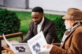 senior man in and african american man reading newspapers together on street