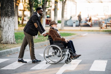 side view of senior disabled man in wheelchair and young african american cuidador riding by street