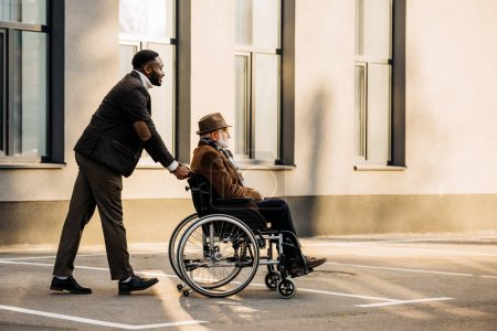 Photo for Side view of senior disabled man in wheelchair and handsome african american cuidador riding by street - Royalty Free Image