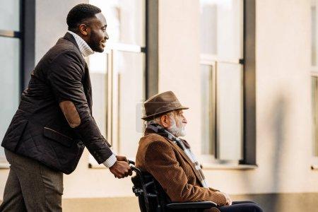 Foto de Vista lateral del senior hombre discapacitado en silla de ruedas y afroamericanos cuidador del montar a caballo por la calle - Imagen libre de derechos