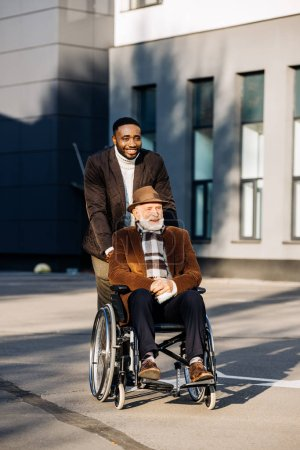 smiling senior disabled man in wheelchair and african american cuidador riding by street