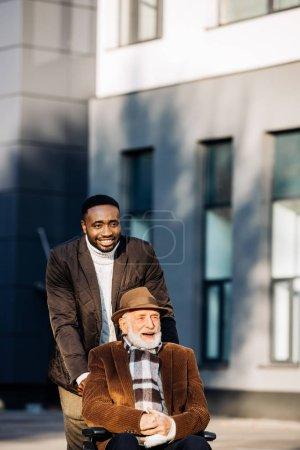 Photo pour Heureux principal désactivé homme en fauteuil roulant et afro-américains cuidador riding de rue - image libre de droit