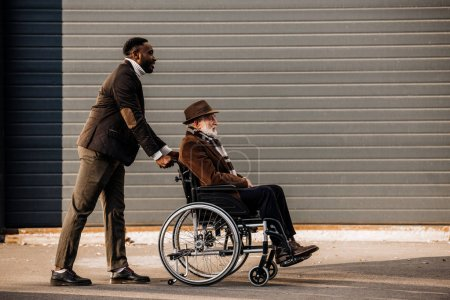 Photo for Side view of senior disabled man in wheelchair and african american man riding by street - Royalty Free Image
