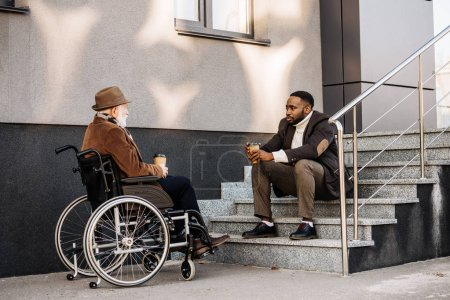 senior disabled man in wheelchair and african american cuidador drinking coffee together and chatting on street