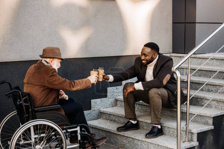 senior disabled man in wheelchair and african american man drinking coffee together and clinking paper cups on street