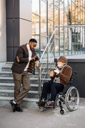 senior disabled man in wheelchair and african american man drinking coffee together on street
