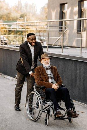 Photo pour Heureux principal désactivé homme à homme en fauteuil roulant et afro-américains monté par rue - image libre de droit