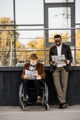senior disabled man in wheelchair and handsome african american man reading newspapers together on street