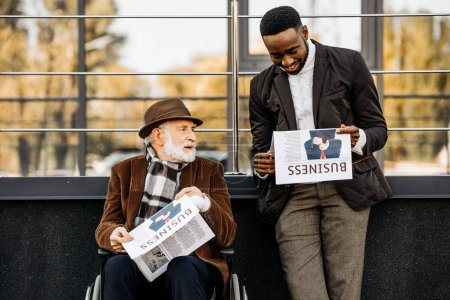 senior disabled man in wheelchair and happy african american man reading newspapers together on street