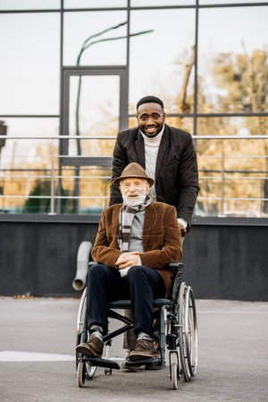 senior disabled man in wheelchair and african american man riding by street
