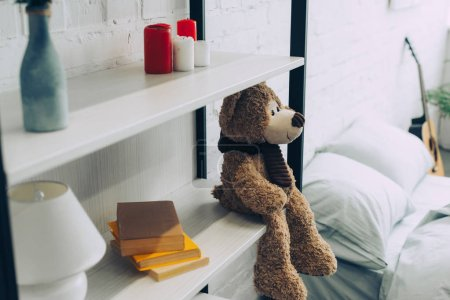 Photo for High angle view of teddy bear sitting on shelves with books and candles at home - Royalty Free Image