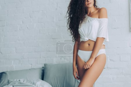 partial view of seductive curly woman in white underpants in bedroom at home