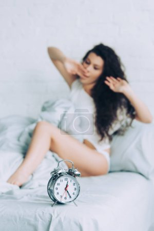 selective focus of alarm clock on bed and woman waking up during morning time in bedroom at home